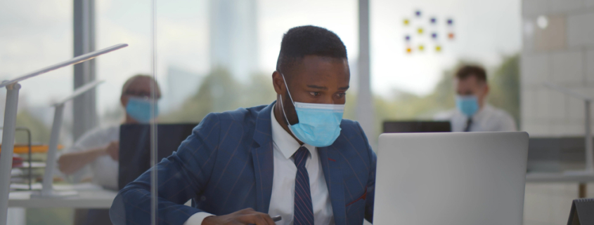 African American man in suit with face mask on